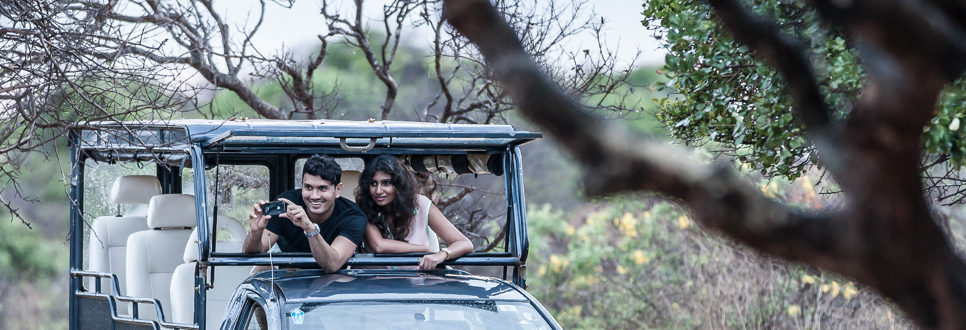 couple on safari at yala, taking a picture of wildlife
