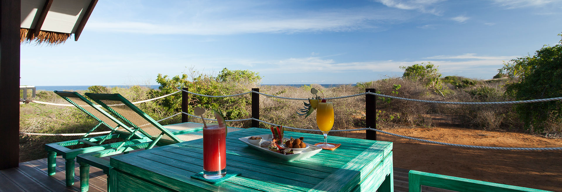 Fresh Juice and food layed out on the table with a view of the clear blue sky
